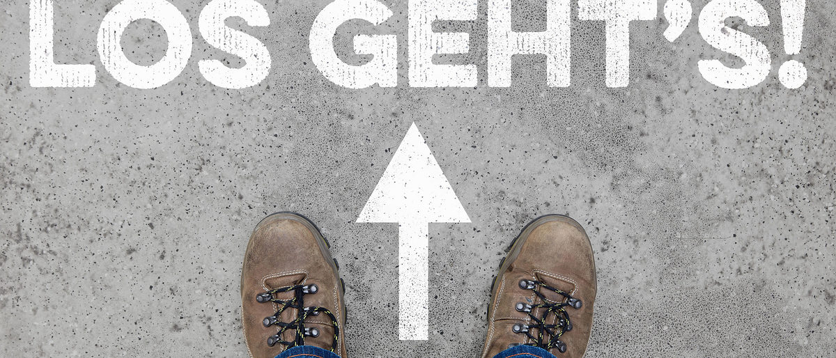 "German slogan ""Los geht's"" (Let's go) with arrow as start concept on a street Schlagwort(e): start, target, goal, beginning, concept, business, career, advice, service, job, motivation, training, future, text, new, marketing, sport, work, profession, coaching, make, successful, arrow, shoes, street, way, background"